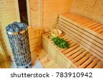 Interior of wooden finnish sauna with birch broom, bucket and stove. The Finnish sauna is a substantial part of their culture.