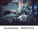 The young auto mechanic dismantles the opposing engine for diagnosis and repair at the stand in the workshop. - stock photo