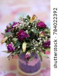 Small photo of Bouquet from dry flowers in a handmade vase on a motley background it is vertically . Flower composition with the dried flowers of a rose and a gipsofila. Gypsophila. Caryophyllaceae Family.