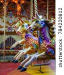Small photo of Three brightly coloured named garish carousel horses (front one called Eileen)