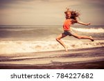 teen girl jumping on the beach... | Shutterstock . vector #784227682