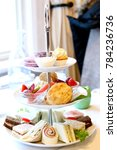 Small photo of elegant afternoon high tea with finger sandwiches and sweets