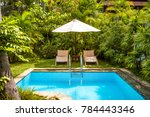 Pool with umbrella and beach beds in a tropical hotel. Beautiful swimming pool in the courtyard. Pool with blue clean water in the garden.