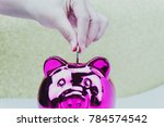 putting coin into the piggy bank | Shutterstock . vector #784574542