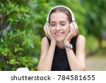 Small photo of Portrait of beautiful woman wearing white headphone enjoin the favorite song while sitting with book and coffee on table relaxing from reading outside in backyard.