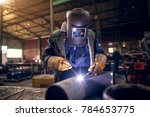 Small photo of Close up portrait view of professional mask protected welder man in uniform working on the metal sculpture at the table in the industrial fabric workshop in front of few other workers.