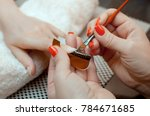 Small photo of The master of the nail polish puts a fixative on the finger before making the nails gel in the beauty salon. Professional care for hands.