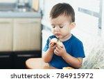 the little boy in the kitchen... | Shutterstock . vector #784915972