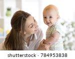 happy baby near to mom in her... | Shutterstock . vector #784953838