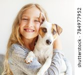 Stock photo happy child with dog portrait girl with pet jack rassell with teen embracing 784977952