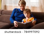 grandmother reading a tale to... | Shutterstock . vector #784997092