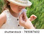 little girl sniffing the scent... | Shutterstock . vector #785087602