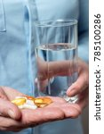 Small photo of Woman take in the hand variety medication pills, yellow capsules of omega 3, glucosamine and calcium dietary supplements and glass with water in the other hand.
