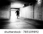 Monochrome of a man fleeing a grungy underground parking.