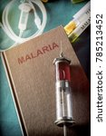 Small photo of Vintage Syringe On A Book Of Malaria, Medical Concept