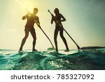 paddleboarding at sunset. young ... | Shutterstock . vector #785327092