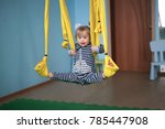 Small photo of child with Down syndrome is engaged in yoga, a yellow hammock and the atmosphere of a children's center, a concept childhood