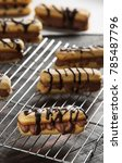 Small photo of Delicious Eclair on Wooden Background