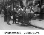 Small photo of Baked potato vendor with a pushcart oven in New York's Lower East Side, c. 1915-20. The neighborhood was packed with Eastern European Jewish immigrants