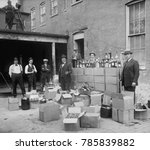 Small photo of Prohibition agents stand with boxes and bottles of wine and liquor after a raid in Wash. D.C. area. Oct. 14, 1922. Note the camera man in upper left