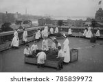 Small photo of Children's roof garden at Ellis Island offered relief from boredom for young detainees, c.1910s. They were held back from U.S. entry because a parent was quarantined. Some of the girls wear long shirt
