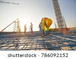 Construction workers fabricating steel reinforcement bar at the construction site - stock photo