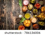 Small photo of Preserved vegetables in glass jars with seamer. On a wooden background.