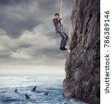 Small photo of Businessman is likely to fall into the sea with sharks. concept of problems and difficulty in business