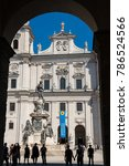 Small photo of Visitors standing at the cathedral square and admiring the baroque architecture of the Salzburg Cathedral in Salzburg, Austria