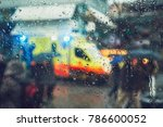 Small photo of Emergency medical service response in the city. Ambulance cars on the rush street during rain. View through a car window and selective focus on the raindrop. Prague, Czech Republic.