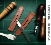 Small photo of Handmade leather watch strap with pricking iron,stitching thread,burnish and slicker wooden in the leather workshop.Leather craft and DIY crafting tools on craftsman's work desk.Handmade ,DIY Concept.
