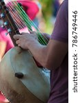 Small photo of Portland, Oregon,USA - August 17,2014: Hawthorn Street annual Community Event. Close up of a street muscian playing a string insturment called the Kora.