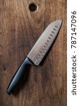 Small photo of The knife lies on the old wooden surface. Knife Santoku. Professional chef's knife.