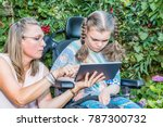 Small photo of Disability a disabled child in a wheelchair sitting outside looking at a tablet computer together with a voluntary care worker