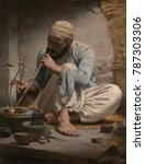 Small photo of THE ARAB JEWELER, by Charles Sprague Pearce, 1882, American painting, oil on canvas. An Arab artisan is painted with strong sense of light and volume. The artist studied in Paris and traveled to Egypt