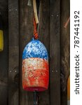Small photo of Owl's Head, Maine, USA - 8/23/2015: Two colorfully painted Styrofoam lobster trap buoys hang on a rustic shed wall. Buoys are color coded to identify their owners.