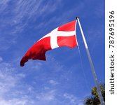 Small photo of Flags / Denmark: The Danish national flag Dannebrog is fluttering in the gusty coastal wind on Laesoe island