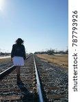 Woman Walking On Railroad...