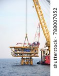 Small photo of Offshore wellhead platform topside being placed on top of the jacket by derrick lay vessel