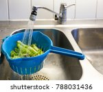 Small photo of Plastic colander or cullender or strainer filled with lettuce being rinsed clean in kitchen sink under the water tap