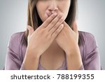 Stock photo asian woman in purple nightgown use both hands close mouth for not commenting or refusing against 788199355