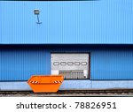 Orange waste container in front of a factory building with blue cladding - stock photo