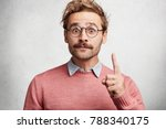 Small photo of Handsome bearded man has trendy hairdo and mustache raises fore finger as gets good idea, has intriguing and clever expression, expresses his confidence, isolated over white concrete background