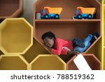 Small photo of a naughty preschool boy playing around in the slot pigeonhole box in classroom