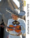 Small photo of Puerto Vallarta, Jalisco / Mexico - 10/01/2016: Mariachi Plays a Violin for Beach Audience Wearing Traditional White Suit, Charro Shirt, Sombrero Hat and Mexican Bow Tie