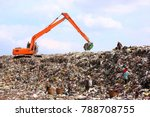 Backhoe working on garbage dump in landfill. People Working at Landfill site.