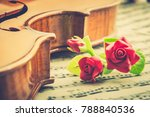 Small photo of Valentine's day / eternal love or special occasion concept : Artificial three red roses put near a stradivarius type violin on blurred musical notes in a romantic love song sheet music. Vintage style.