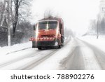 Small photo of Snowplow cleaning streets in the aggravated traffic due to strong snowfall.
