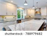 Stock photo luxury home interior boasts amazing kitchen with custom white shaker cabinets endless marble 788979682