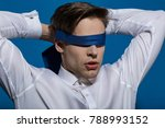 Small photo of Man blindfolded with necktie on blue background. Blindfold business concept. Fashion, accessory, style.